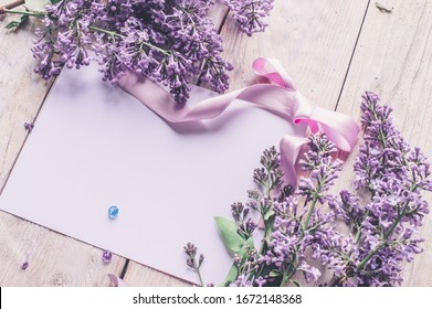 Spring flowers. Lilac flowers on white wooden background. Top view, flat lay with copy space