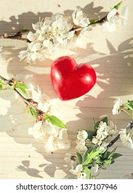 spring flowers and red heart candle on wooden table