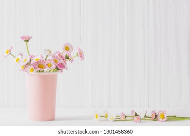 spring flowers in vase on white wooden background