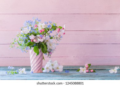 spring flowers in vase on wooden background