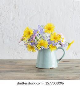 spring flowers in vintage jug on wooden table