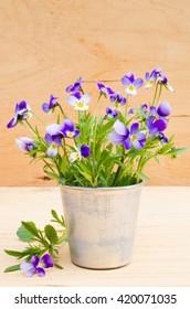 Spring flowers in vintage vase on wooden background, rustic style.