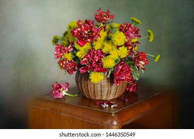 Spring flowers.Bouquet of yellow dandelions and red tulips in a basket on a green background.