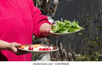 Spring food, eating outside, diet concept. Woman bringing to table in the garden two plates with cheese, radishes and fresh lettuce.
