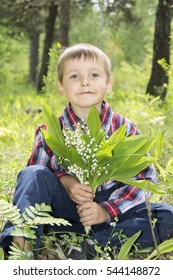 Spring in the forest funny little boy holding a small bouquet lily of the valley.