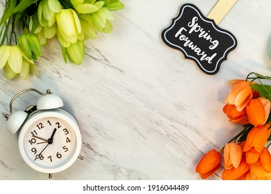 Spring Forward Daylight Saving Time concept with text on marble flat lay.  White alarm clock with tulips.