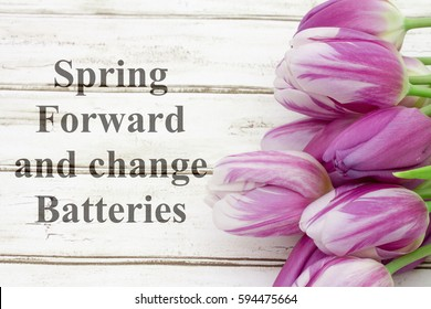 Spring Forward message, A bouquet of purple tulips on weathered wood  with text Spring Forward and change Batteries