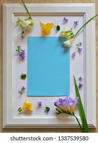 Spring freesia flowers on empty white photo frame