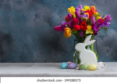 Spring fresh flowers with easter eggs and white pocelane rabbit with copy space on black background