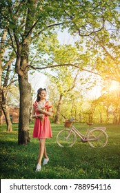 Spring garden colors. Fresh emotions. Beautiful girl wearing a nice pink dress having fun in park with bicycle carrying a beautiful basket full for flowers. Vintage scenery. Cute girl with retro look.
