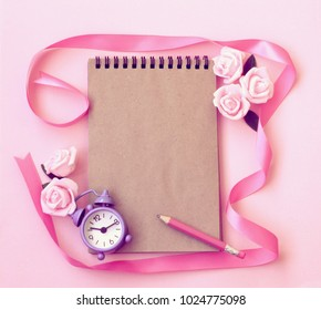 Spring gentle pink paper texture background with alarm clock, rose flowers, pencil, notebook, ribbon, vintage style, mock up