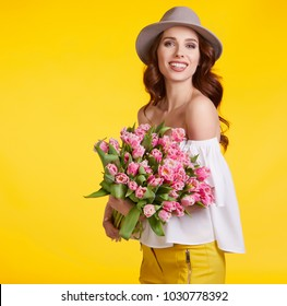 Spring girl iwith flowers tulips in hands on a light background