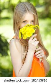 Spring girl. Lovely blond girl smelling bunch of dandelions outdoors.