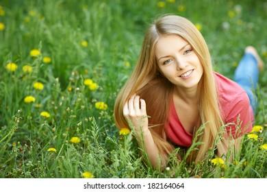 Spring girl lying on the field of dandelions