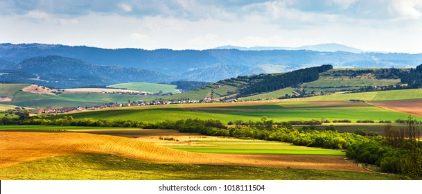 Spring green field and meadows on the hills panorama. Picturesque valley in Tatras mountains of Slovakia. Rural scene. Village and countryside landscape.