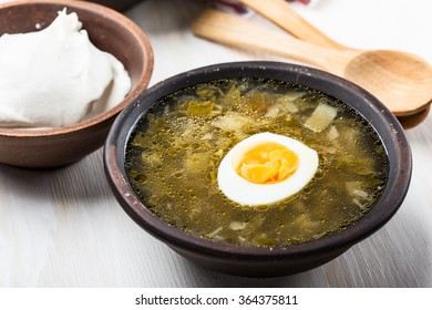 Spring greens borscht, sorrel spinach soup topped with boil egg garnish, creme fraiche