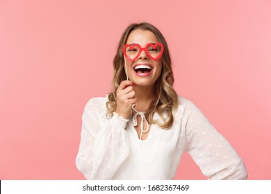 Spring, happiness and celebration concept. Close-up portrait of funny and carefree, beautiful caucasian woman with blond hair, white dress, holding heart-shaped glasses mask and laughing