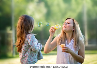 Spring. Happy mother with daughter playing with soap bubbles