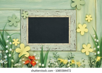 Spring holiday background: blackboard framed with spring flowers on neutral wooden background, space for your text