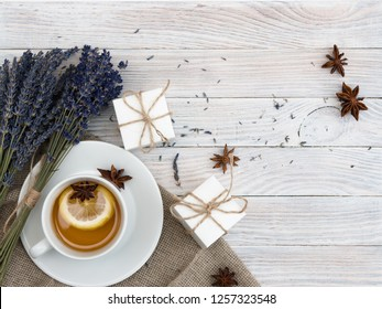 Spring holiday flat ley: lavender, gift boxes with jewelry, bracelet with charms, tea with lemon, vanilla, cinnamon. Congratulate your beloved on the holiday. March 8. Mothers Day. Hugge. Lagom.