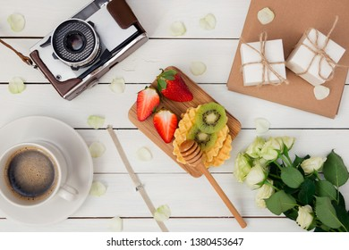 Spring holiday flat ley: roses, gift boxes with jewelry, bracelet with charms, camera,coffee, waffles, strawberries and kiwi. Congratulate your beloved on  holiday. March 8. Mothers Day. Hugge. Lagom.