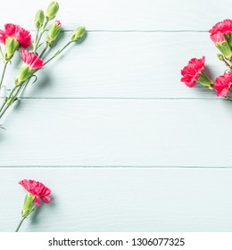 Spring holidays background with bouquet of pink carnation on light turquoise wooden table. Top view with copy space.