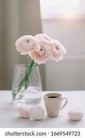 Inneneinrichtung im Frühling. Eine Tasse Kaffee und rosafarbene Rosenblumen in Glasvase im Morgenlicht im skandinavischen Wohnzimmer. Guten Morgen Konzept. Inneneinrichtung des Zimmers mit schönen Blumen