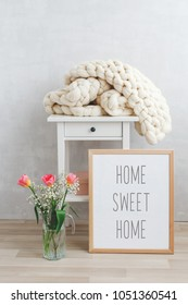 Spring home interior decor: white knitted woolen merino chunky plaid, bedside table, frame with text HOME SWEET HOME, glass vase, tulips flowers. Blanket of thick yarn. Cozy scandinavian room interior