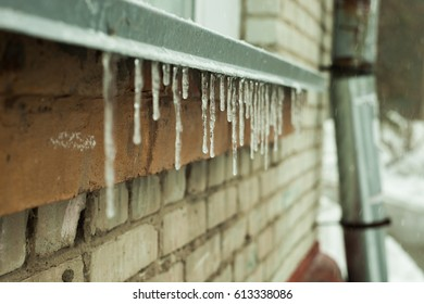 Spring icicles hanging from the roof or eaves of the old brick houses and drain pipe. Spring concept. Selective focus.