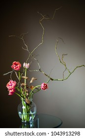 Spring Ikebana with pink tulips in glass vase, dark background
