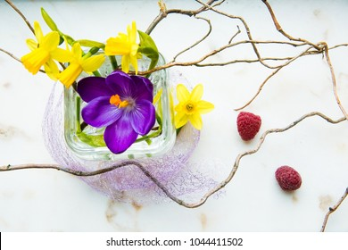 spring ikebana with yellow narcissus and crocus. little bouquette on white mramor background