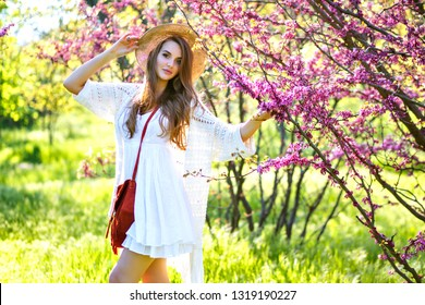 Spring Image of youth elegant pretty woman wearing feminine white boho outfit and straw hat posing at blooming gardens, flowers of Sakura, summer trends.