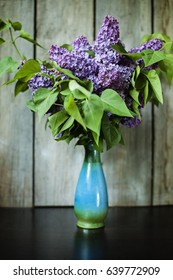 Spring interior concept with bright lilac flowers in a vintage vase on rustic wooden table blurred background toning