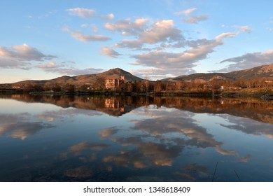 Spring lake landscape with palace mountains clouds and sunset reflections