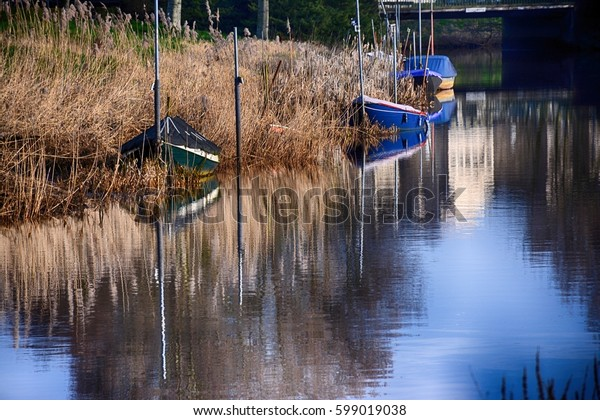 Spring landscape. Boats reflecting in the river in spring morning.