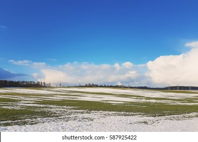 spring landscape in Europe. melting snow, green grass and blue skies with clouds.