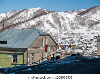 Spring landscape with the facade of a residential house with a view of the snow-covered hill in Petropavlovsk-Kamchatsky