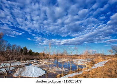 Spring landscape with fiasco, river, forest and clouds on a blue sky