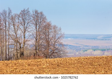 Spring landscape. Freshly plowed field. hilly terrain. trees without leaves. Multicolored spring trees. Snow left over from last year's winter. The last snow.