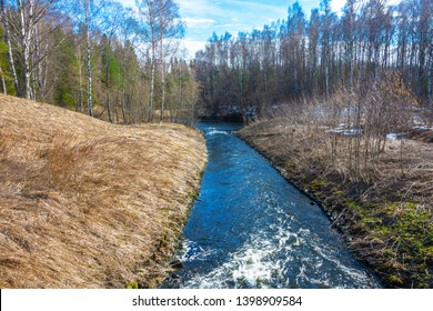 Spring landscape with a small fast river and banks covered with forest on a sunny day.