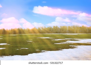 spring landscape snow melt in the field and white clouds on blue sky on a sunny day