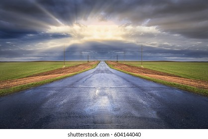 spring landscape wet road leading to the horizon amid green fields and cloudy sky
