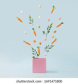 Feuilles de printemps, oeufs de Pâques et carottes sortent de la boîte rose. Concept nature printanier. Idée d'arrière-plan de vacances de Pâques.