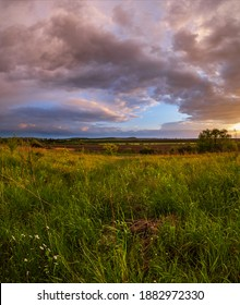 Spring meadow after rain, cloudy evening pre sunset sky, rural hills and fields in far. Natural seasonal, weather, climate, countryside beauty concept scene.