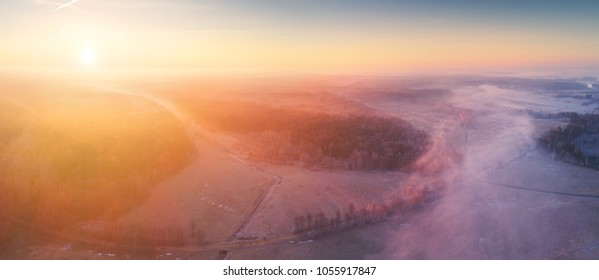 Spring misty landscape from above. Rising sun illuminate fog over field. Agricultural background.
