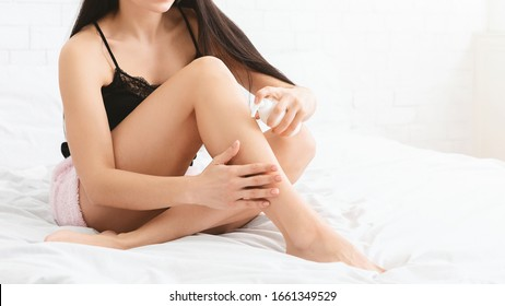 Spring moisturizing of skin. Young woman applying lotion on her legs, sitting on bed, panorama