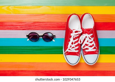 Spring mood clothes, gumshoes and eyeglasses on rainbow multicolored background