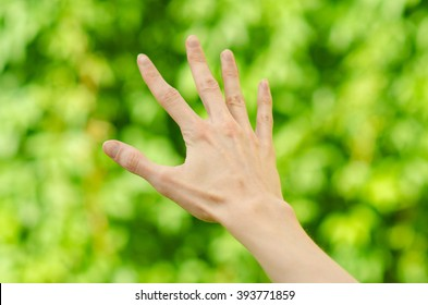 Spring and nature theme: man's hand showing gesture on a background of green grass, first-person view