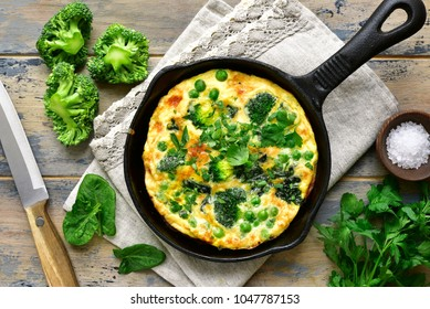 Spring omelette with green vegetables (broccoli, sweet pea and spinach) in a skillet over rustic wooden background.Top view.