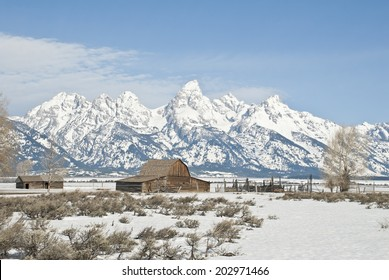 Spring on an old barn and corral stand on a Wyoming ranch with the Teton Peaks towering in the background.